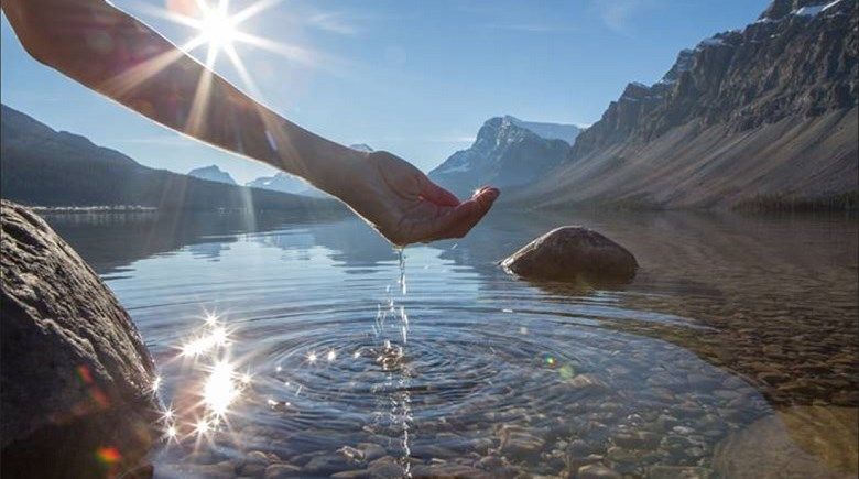Hand scooping water from lake