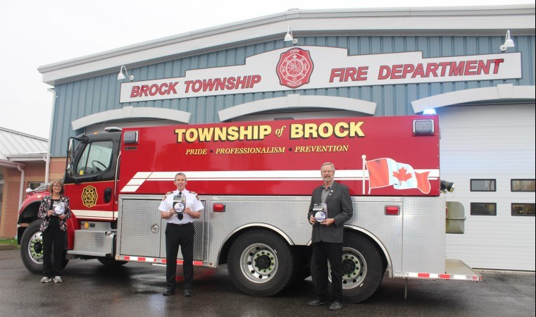 Rick Harrison, Ted Smith and Lynn Campbell in holding award in front of fire truck