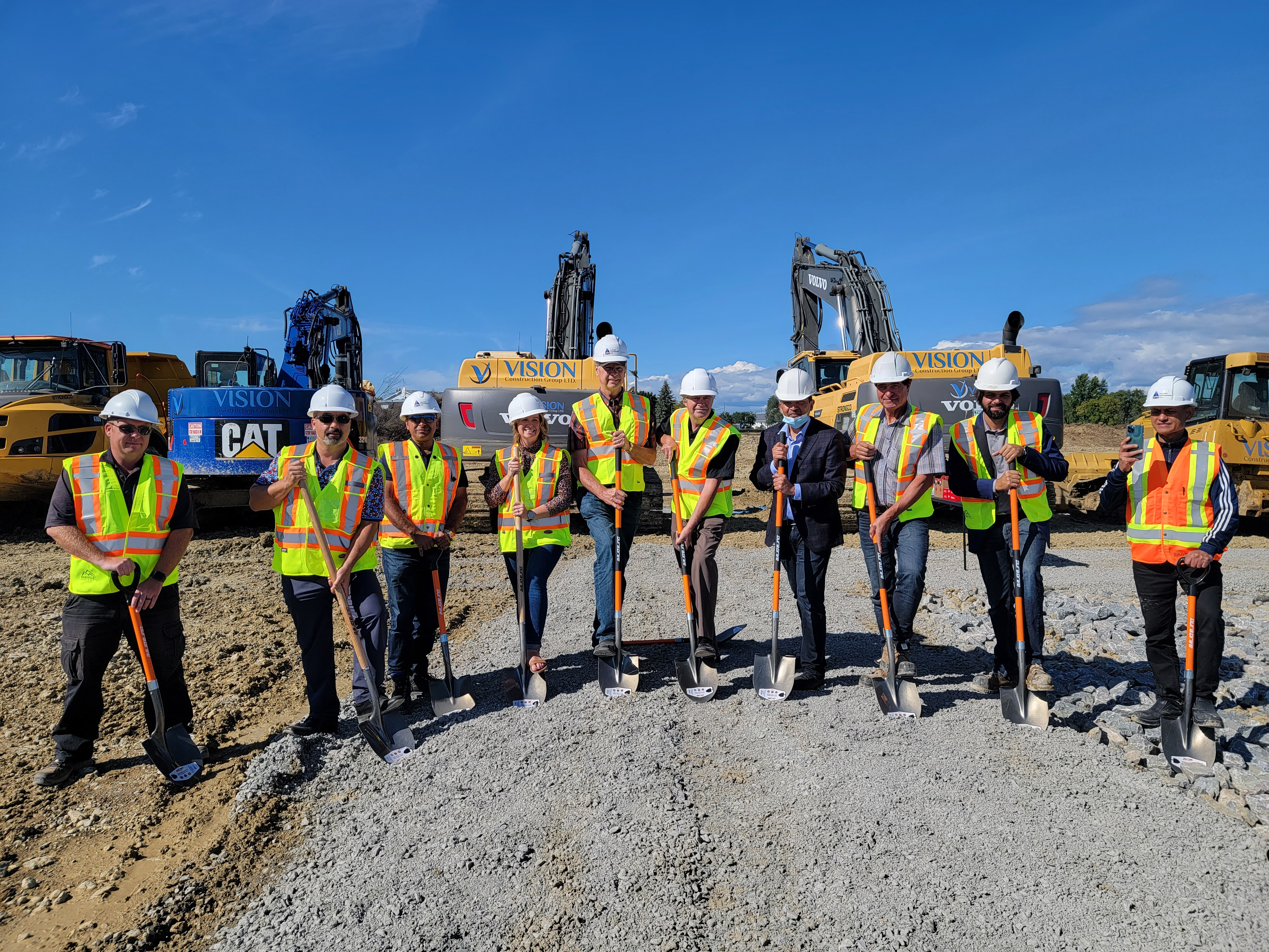 Group standing in construction gear with shovels in hand